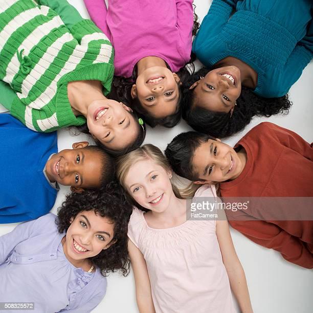 Elementares alunos deitada em um círculo