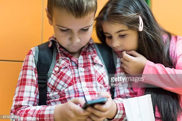 Elementare Schüler lesen eine SMS auf Handy.