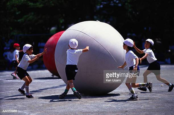 Elementary Students Rolling Balls in a Schoolyard