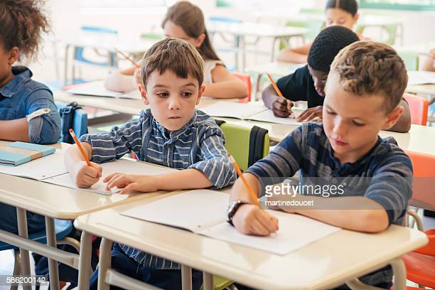 Elementary students taking a test in classroom.