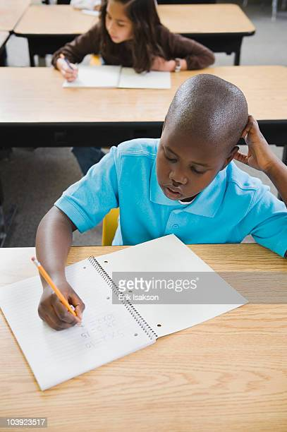 Elementary students writing in notebooks at their desks