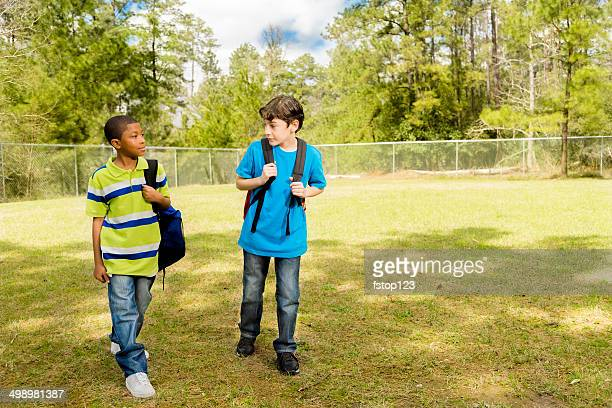 Elementary-age boys walk to school. Campus or park. Friends.