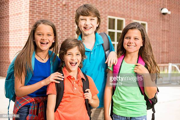 Elementary-age children, friends on school campus going back to school.