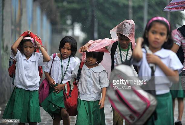 Elementery students leave school after classes were suspended by bad weather caused by typhoon Megi in Manila on October 19 2010 The strongest...