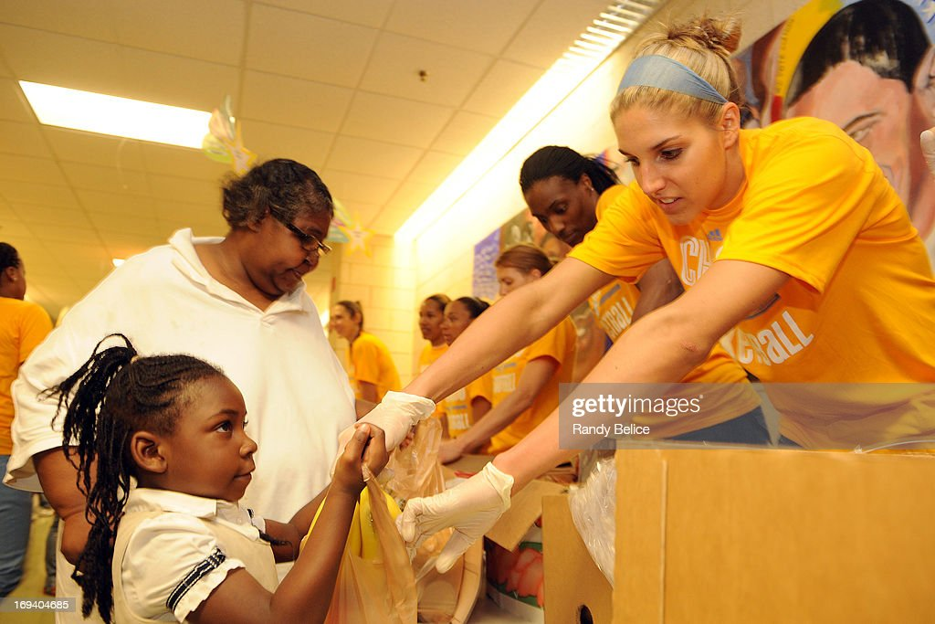 Elena Delle Donne #11 of the Chicago Sky fills a bag with fruit for a young client during a Chicago Sky Cares food distribution event in partnership with the Greater Chicago Food Depostitory on May 22, 2013 at the Jacob Beidler Elementary School in Chicago, Illinois. The event is part of the WNBA Cares week of service activities.