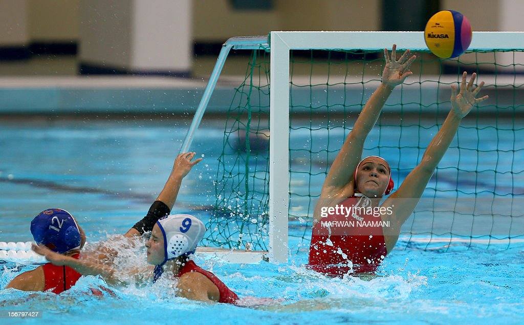 Elena Dukhanova, goal keeper of Uzbekistan tries to save a shot by Lel Zhang of China (L) under the pressure of Liliya Umarova (C) of Uzbekistan during the two teams water polo game in at the 9th Asian Swimming Championships in Dubai, on November 21, 2012.