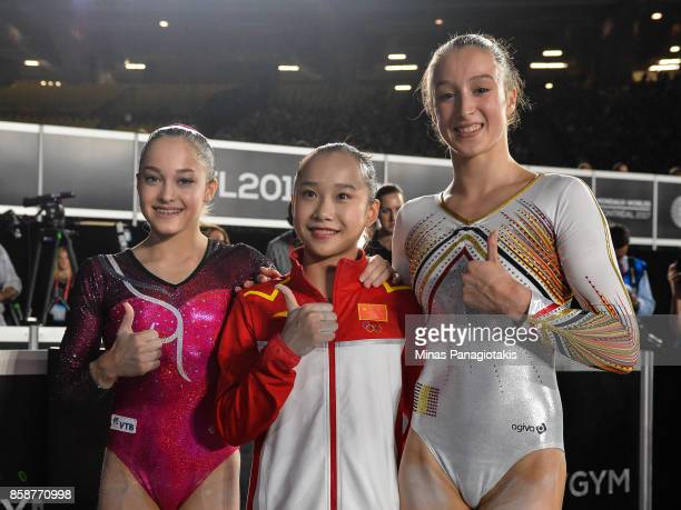 Elena Eremina of Russia Yilin Fan of People's Republic of China and Nina Derwael of Belgium pose for photos after competing on the uneven bars during...