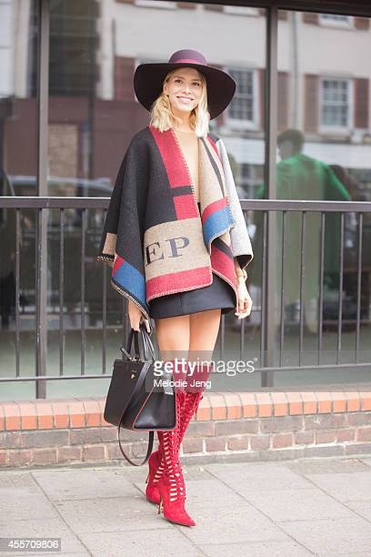 Elena Perminova enters Topshop in a Burberry cape and Longchamp bag during London Fashion Week Spring Summer 2015 at on September 14 2014 in London...