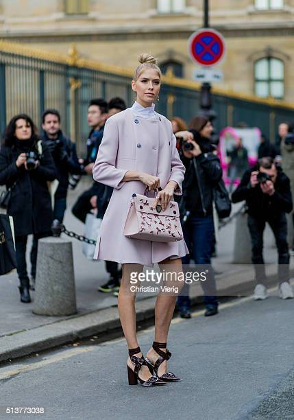 Elena Perminova is wearing a pink wool coat and Dior bag outside Dior during the Paris Fashion Week Womenswear Fall/Winter 2016/2017 on March 4 2016...