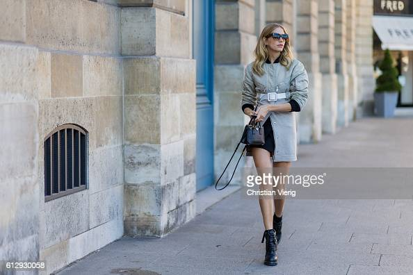 Elena Perminova wearing a coat belt and Prada mini bag outside Louis Vuitton on October 5 2016 in Paris France