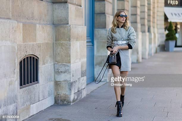 Elena Perminova wearing a coat belt and Prada mini bag outside Louis Vuitton on October 5 2016 in Paris France