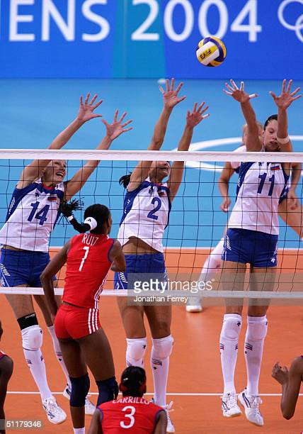 Elena Plotnikova Irina Tebenikhina and Ekaterina Gamova of Russia attempt to block a spike in the women's indoor Volleyball preliminary match on...