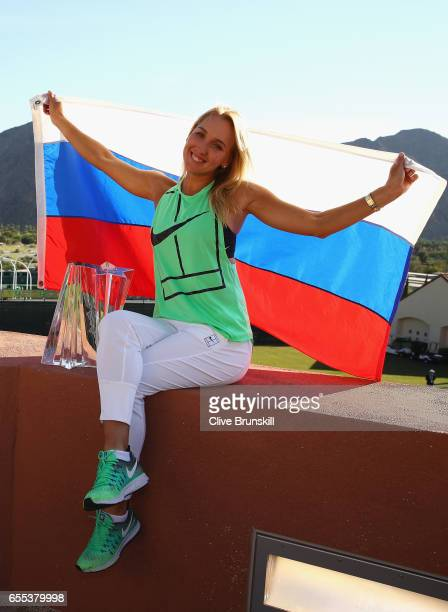 Elena Vesnina of Russia holds the Russian flag along with her trophy as she poses for photographs after her three set victory against Svetlana...