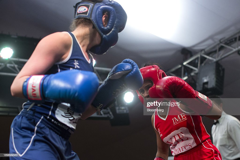 Eleni Himaras, a Bloomberg News reporter, in blue, exchanges blows with Devi Kumar, associate director for sales and marketing, human resources and professional support at Charterhouse Partnership, in the fifth bout during the Hedge Fund Fight Nite 2013 charity fighting event in Hong Kong, China, on Thursday, May 30, 2013. The event raises money for Operation Breakthrough and Operation Smile charities. Photographer: Jerome Favre/Bloomberg via Getty Images