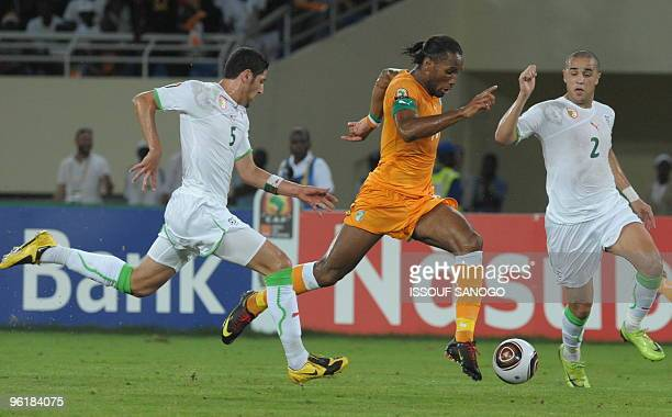 Elephant Ivory Coast National football team striker and team captain Didier Drogba duels for the ball with Algeria's Madjid and Rafic Halliche on...