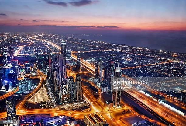 Elevated cityscape of Dubai illuminated at dusk
