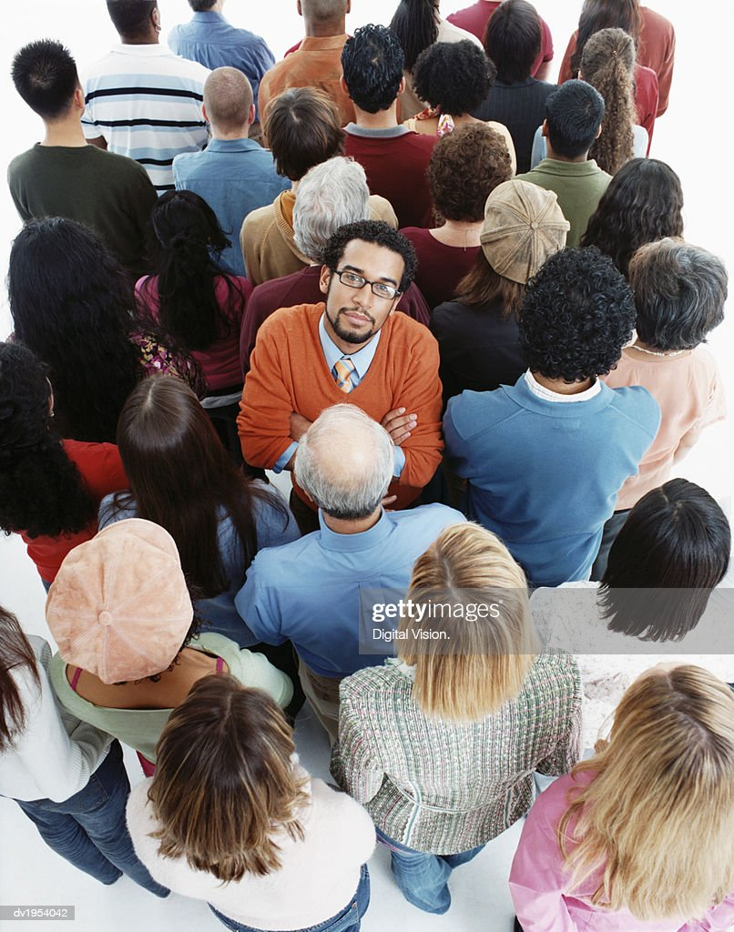 Elevated Studio Shot of a Well Dressed Man Standing in a Crowd of People With Their Backs Turned, Looking at the Camera : Stock Photo