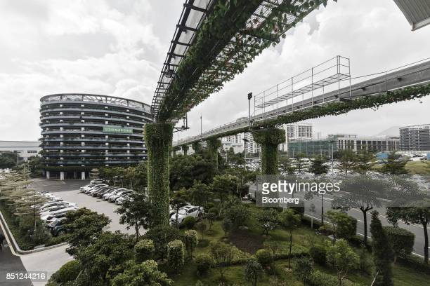 Elevated tracks for the BYD Co SkyRail monorail system stand in front of a charging parking lot tower left at the company's headquarters in Shenzhen...
