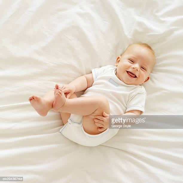 elevated view of a baby (12-18 months) lying on a bed