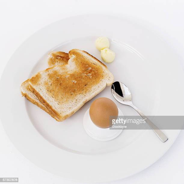 Elevated view of a boiled egg served with toast and butter