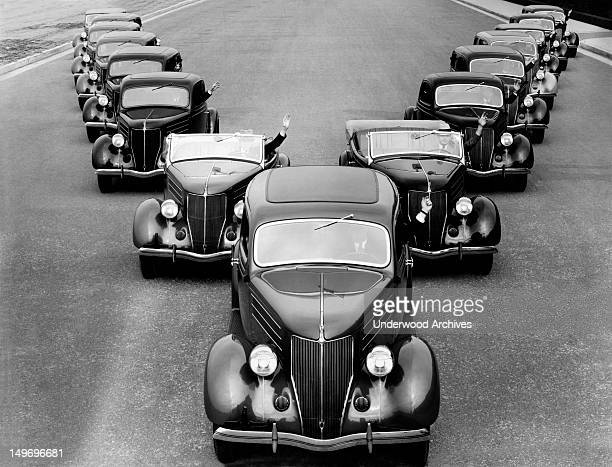 A fleet of fifteen Cadillacs driving down the street in a 'V' formation mid 1930s