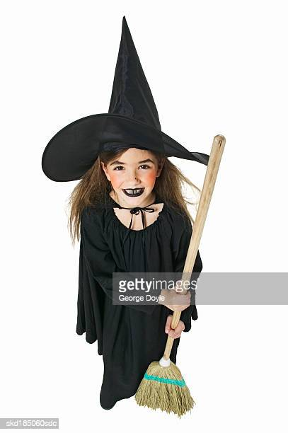 elevated view of a girl (10-11) dressed as a witch and holding a broom