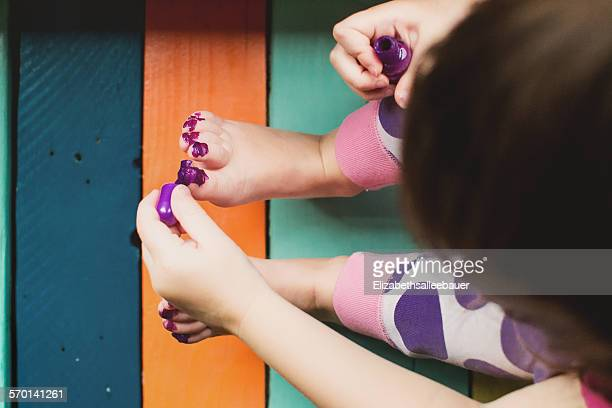 Elevated view of a girl messily painting her toes