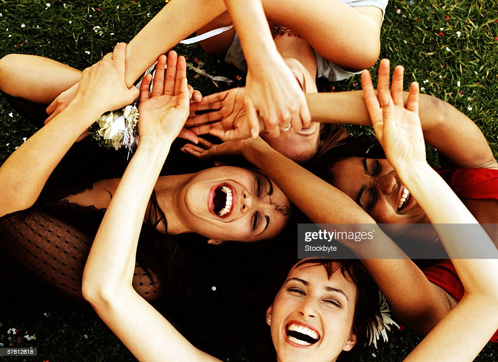 Elevated view of a group of young women lying on a lawn with their hands together : Stock Photo