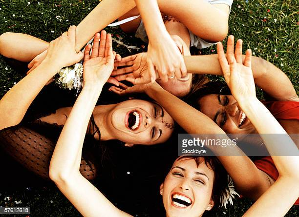 Elevated view of a group of young women lying on a lawn with their hands together