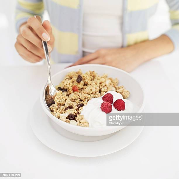 Elevated view of a human hand holding a spoon in a bowl of cereal