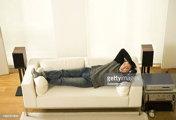 Elevated view of a mid adult man listening to music while lying on a couch in the living room