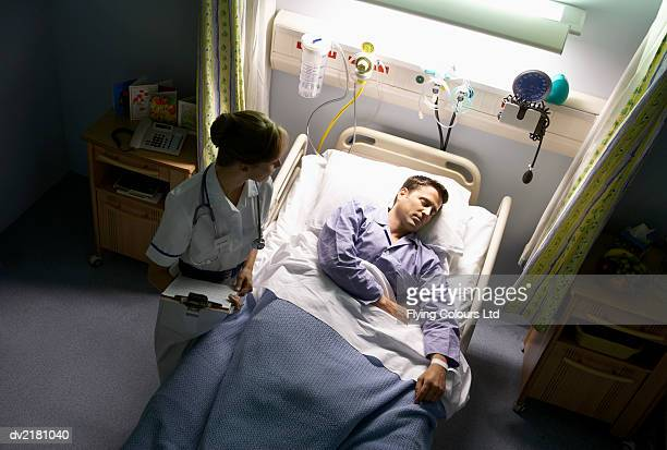 Elevated View of a Nurse Standing by a Male Patient's Hospital Bed at Night