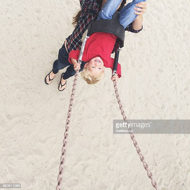 Elevated view of a woman pushing her son on a swing