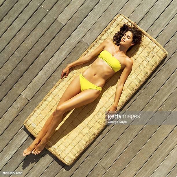 Elevated view of a woman wearing a bikini lying on a straw mat