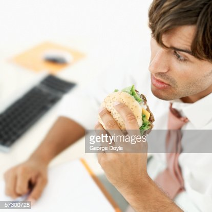 Elevated view of a young businessman eating a hamburger at his desk