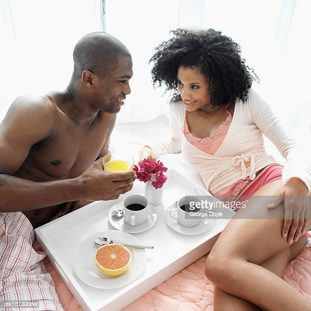 Elevated view of a young couple having coffee in bed