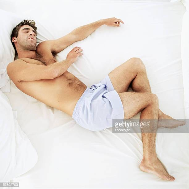 Elevated view of a young man sleeping in bed