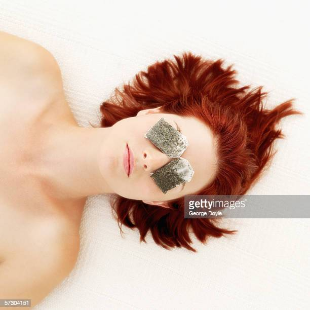 Elevated view of a young woman lying down with teabags on her eyes
