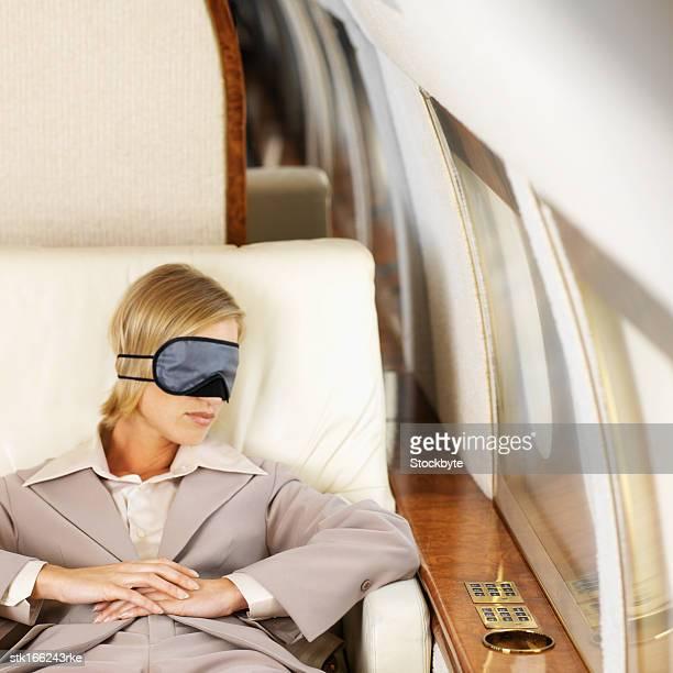 elevated view of businesswoman sleeping wearing eye mask
