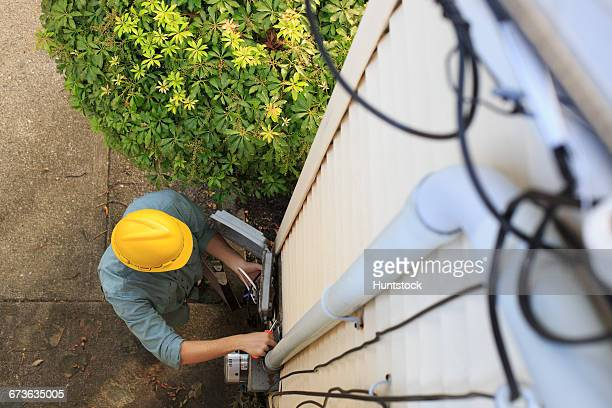 Elevated view of cable installer working on house access point