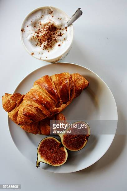Elevated view of croissants, figs and a cappuccino