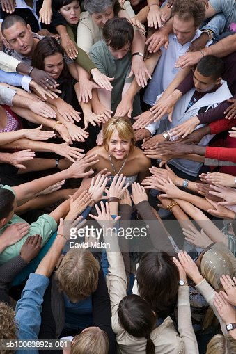 Elevated view of crowd surrounding woman, reaching toward her : Stock Photo