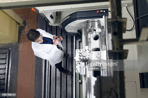 Elevated view of female worker handling machine
