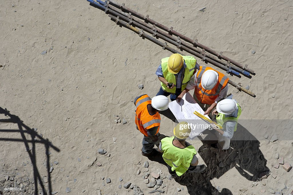 Elevated View of Five Builders Standing in a Circle Looking at Plans : Stock Photo