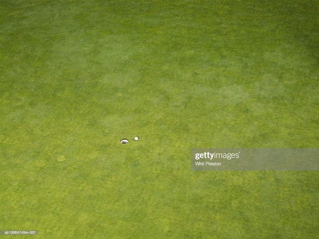 Elevated view of golf course lawn with hole and ball : Stock Photo