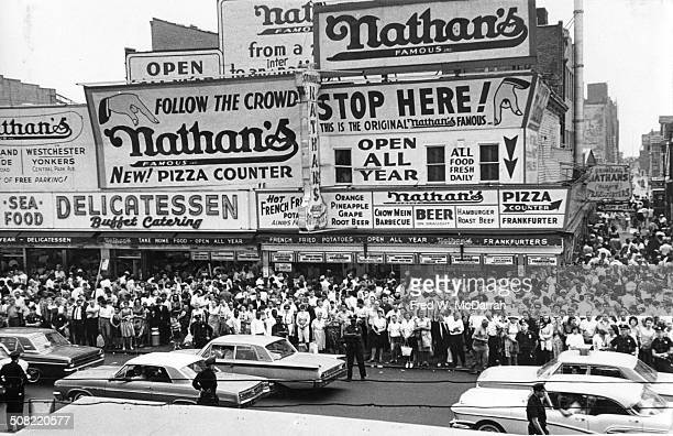 Elevated view of huge crowd of people gathered on the sidewalk during a political rally outside Nathan's Famous fast food restaurant Coney Island New...