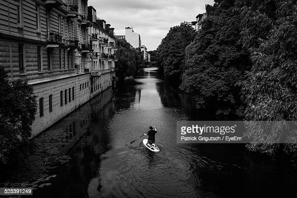 Elevated View of Man Using Paddleboard On Flooded Street