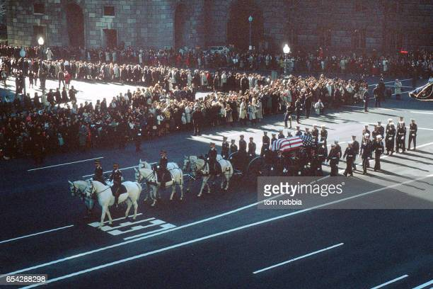 Elevated view of President John F Kennedy's funeral procession shows the flagcovered casket on a horsedrawn caisson as it travels down Pennsylvania...
