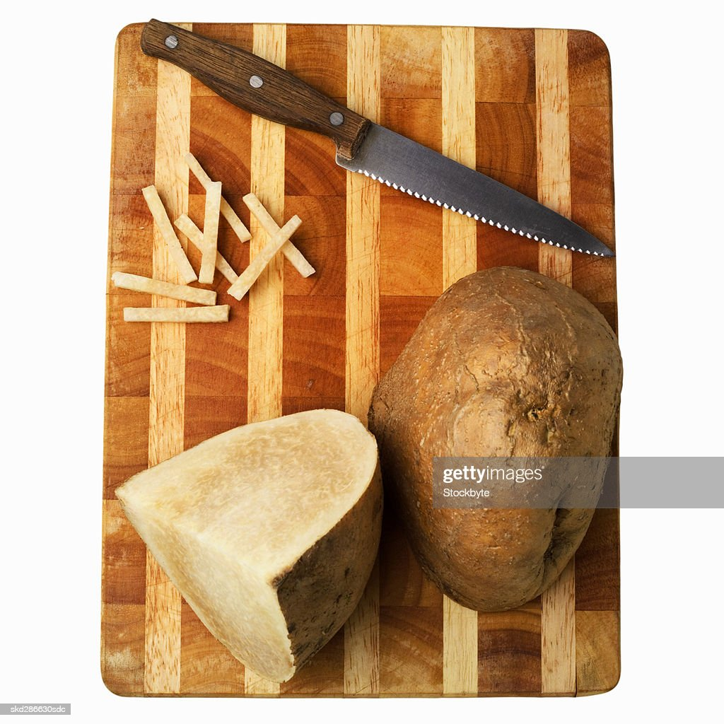 Elevated view of sliced jicama and a knife on a cutting board : Stock Photo