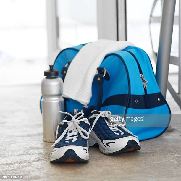 Elevated view of sports bag and water bottle and running shoes and a towel